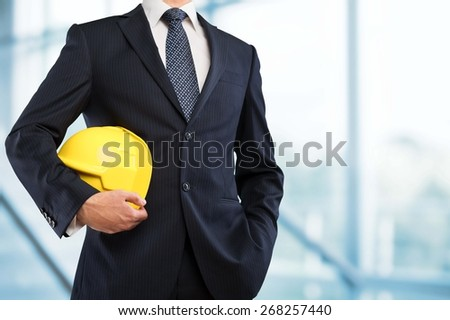 Engineering. Engineer yellow helmet for workers security on the background of a new high-rise apartment buildings and construction cranes and evening sunset sky - stock photo
