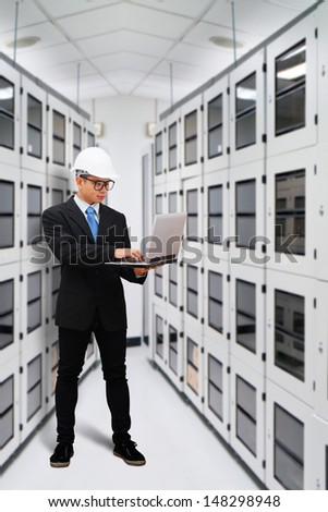 Engineering in data center room with laptop - stock photo