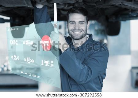 Engineering interface against mechanic examining under the car - stock photo