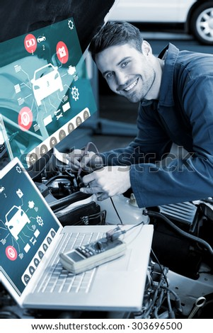 Engineering interface against mechanic using laptop on car - stock photo