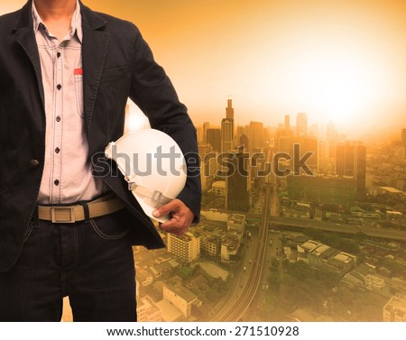 engineering man and sun light behind urban construction background use for land development theme - stock photo