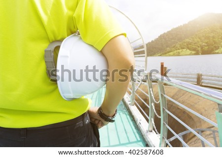 Engineering man standing with white safety helmet, natural golden sunlight at background. - stock photo