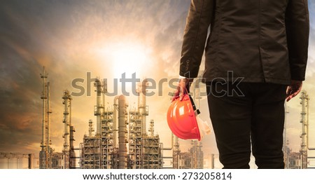 engineering man with safety helmet standing in industry estate against sun rising above oil refinery plant  - stock photo