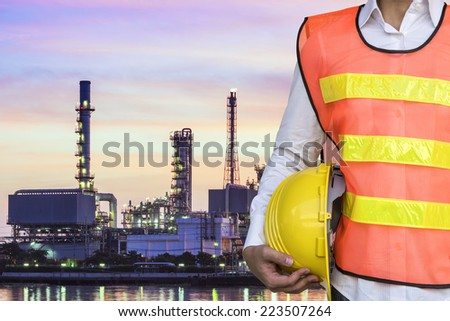 engineering man with yellow safety helmet standing in front of oil refinery building industry - stock photo