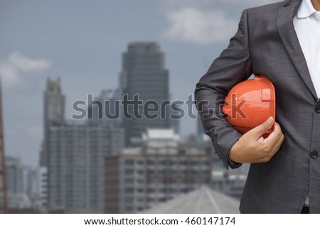 engineering management construction helmet,engineer or worker hold in hand helmet for workers security on the background city scape. - stock photo