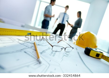 Engineering objects on workplace on background of talking co-workers - stock photo