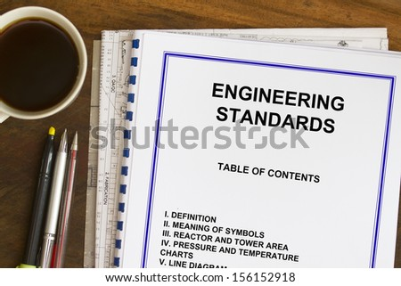 Engineering standards sketch with coffee and blueprints.