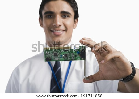 Engineering student holding an electronic circuit board - stock photo