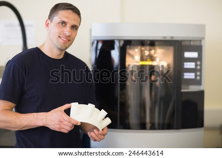 Engineering student holding object printed from 3d printer at the university - stock photo