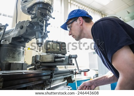 Engineering student using large drill at the university - stock photo