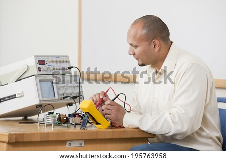 Engineering student using probes for making connections on circuit breadboard for electronics laboratory experiment