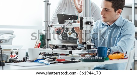 Engineering students using an innovative 3D printer in the laboratory - stock photo