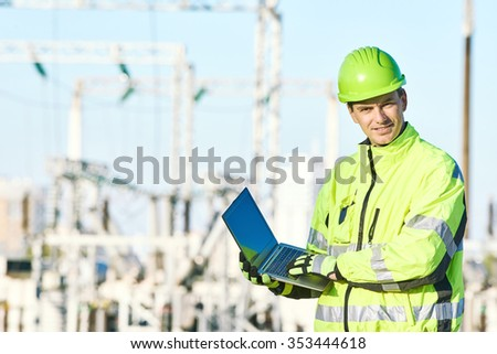 Engineering supervision. Portrait of male service engineer in high visibility reflecting clothing and hard hat working on notebook computer at heat electropower station - stock photo