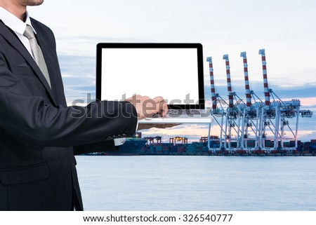 Engineering working hold conputer notebook in front of industrial harbor cargo