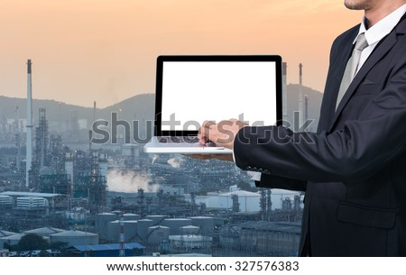 Engineering working hold conputer notebook in front of oil refinery power station