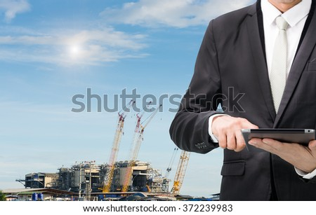 Engineering working hold tablet in front of construction site.