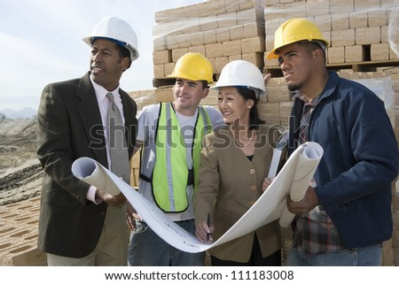 Engineers and workers with blueprint at construction site - stock photo