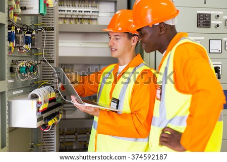 engineers checking distribution box with laptop in control room