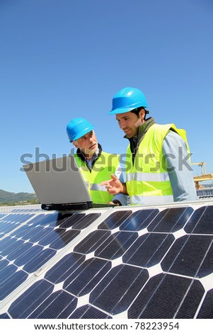 Engineers checking solar panel setup - stock photo
