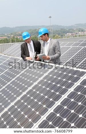 Engineers checking solar panels setup - stock photo