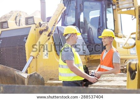 Engineers discussing at construction site - stock photo