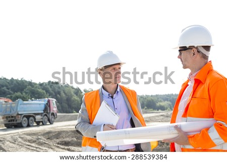 Engineers discussing at construction site against clear sky - stock photo