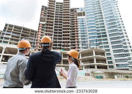 Engineers discussing construction of the building, rear view - stock photo