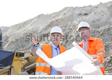 Engineers discussing over blueprint at construction site - stock photo