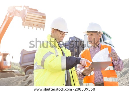 Engineers discussing over documents at construction site - stock photo