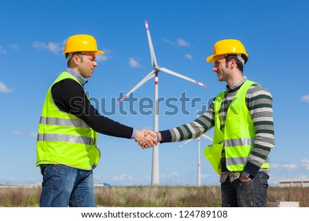 Engineers giving Handshake in a Wind Turbine Power Station - stock photo
