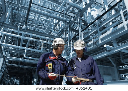 engineers inside refinery with blue toned pipeline menagerie in background - stock photo