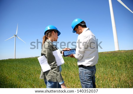 Engineers looking at wind turbine site with tablet