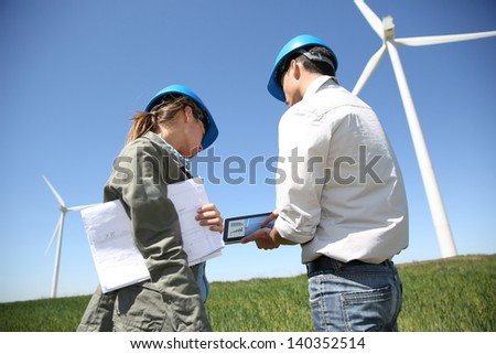 Engineers looking at wind turbine site with tablet - stock photo