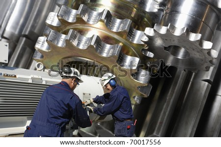 engineers, mechanics in metal and steel-industry, machinery in background - stock photo