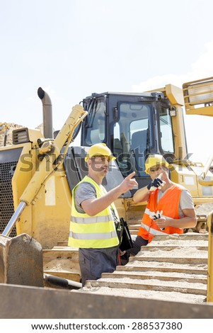 Engineers pointing while discussing at construction site against clear sky - stock photo