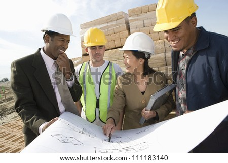 Engineers showing blueprint to workers - stock photo