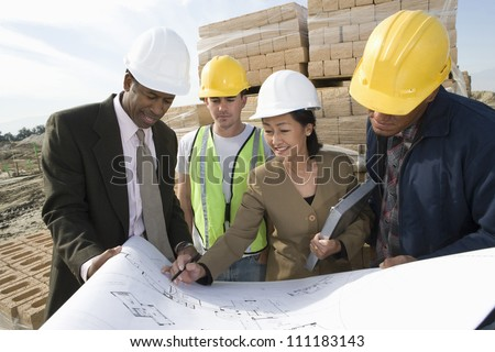 Engineers showing blueprint to workers at construction site