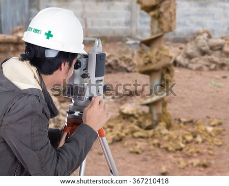 Engineers use tacheometer or theodolite with construction site background - stock photo