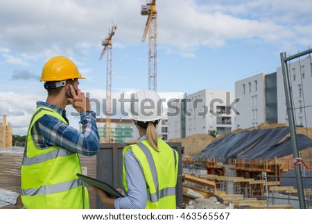 engineers using mobile phone at construction site