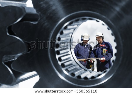 engineers, workers seen through a large cogwheels axle - stock photo