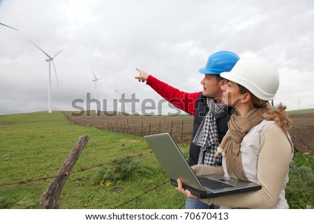 Engineers working by wind turbines field - stock photo