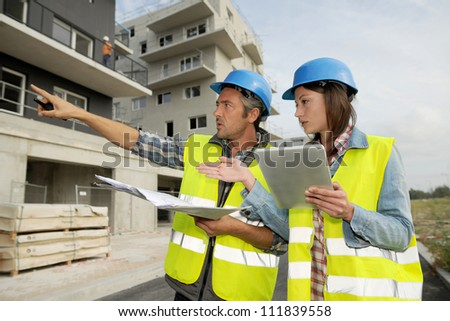 Engineers working on construction site - stock photo
