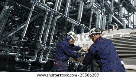 engineers working on refinery machinery, inside large oil industry plant - stock photo