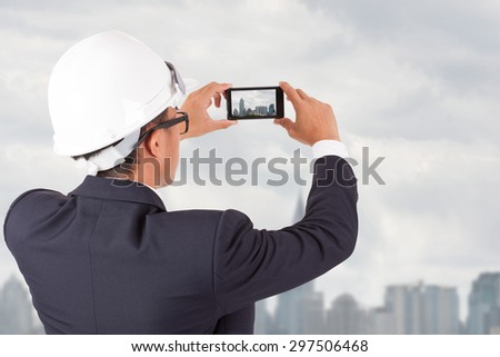 enginerring holding a smartphone mobile cell device, taking pictures of construction project. - stock photo