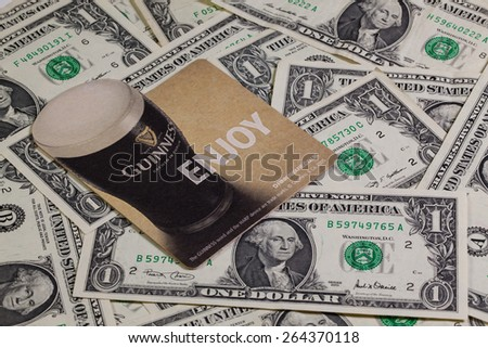 England,London - November 11, 2014:Beermats from Guinness beer and US dollars.Guinness is an Irish dry stout that originated in the brewery of Arthur Guinness at St. James's Gate,Dublin. - stock photo