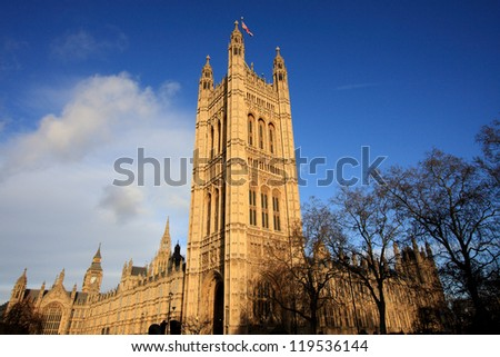 England's Parliament building with deep blue skies rises above Westminster. There's a glimpse of the famous Big Ben, as well. - stock photo