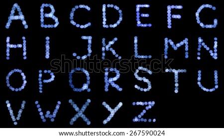 English alphabet, letters of Christmas lights, blue bokeh. - stock photo
