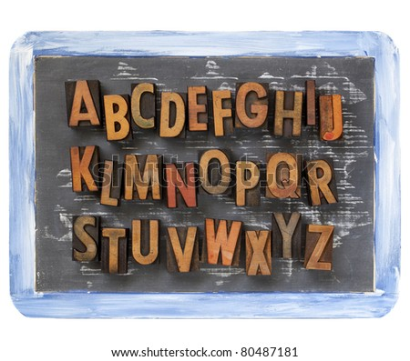 English alphabet - vintage wood letterpress printing blocks on a small slate blackboard with chalk texture and rough blue frame - stock photo