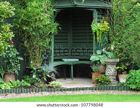 English back Garden with gazebo surrounded with planters