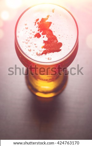 English beer concept, Great Britain silhouette on foam in beer glass on black table. The continents shapes are altered ones from visibleearth.nasa.gov